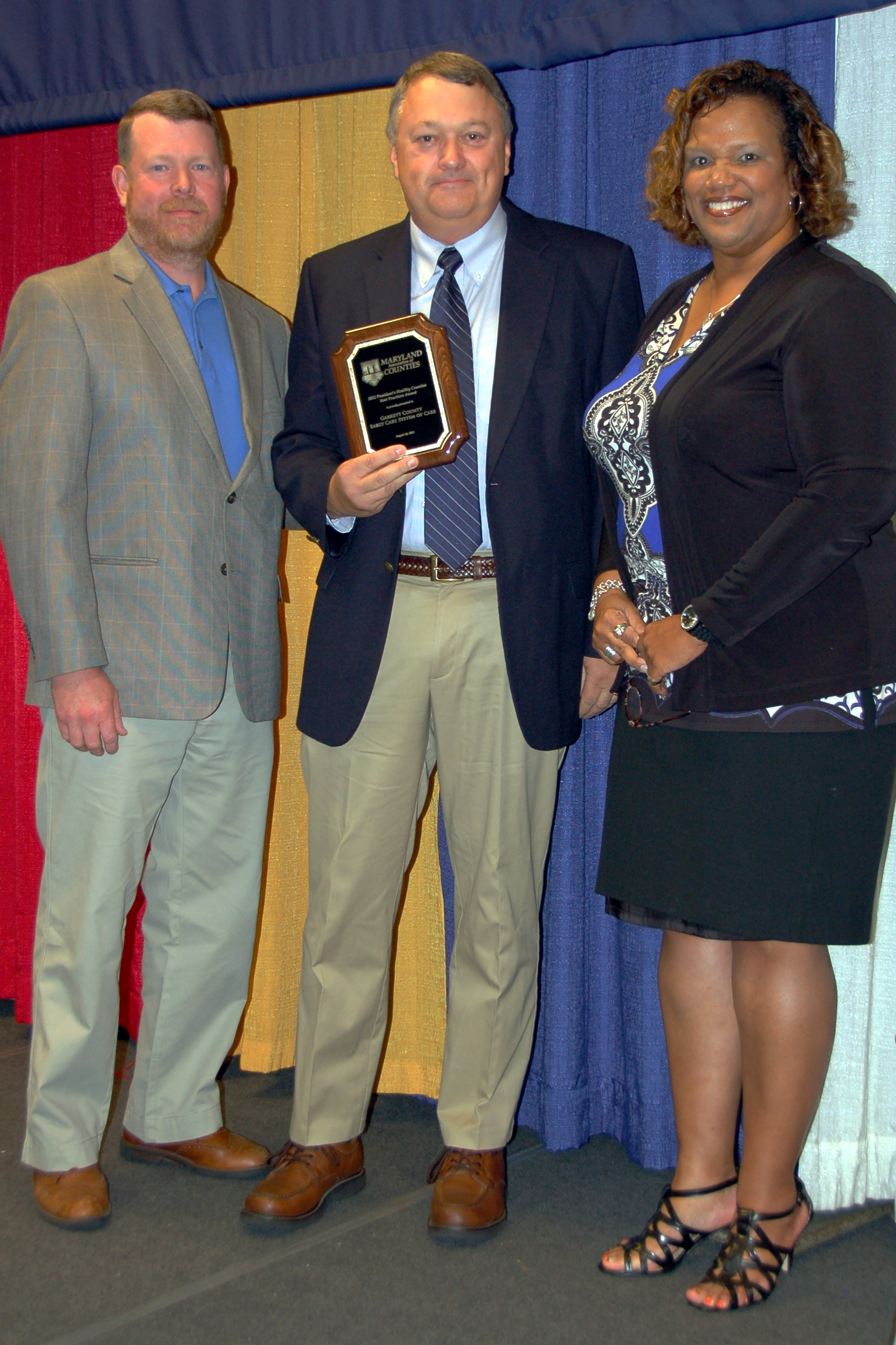 Man holding award next to two individuals